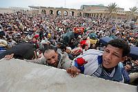 PK nr: 10475.Kategori: Dokumentar utland.Tittel: Exit Libya..Bildetekst: Folk forsøker å klatre over muren som skiller Libya og Tunisia. Krigen i Libya er i gang og folk rømmerkrigshandlingene. I løpet av noen få dager krysset titusenvis grenseovergangen ved Ra´s Ajdir og inn til Tunisia. Mange sov under åpen himmel i dagesvis før de kom inn i flyktingeleire eller ble sendt videre. ..Digitalt.Dato: 28.februar 2011.Sted: Ben Gardene, Tunisia