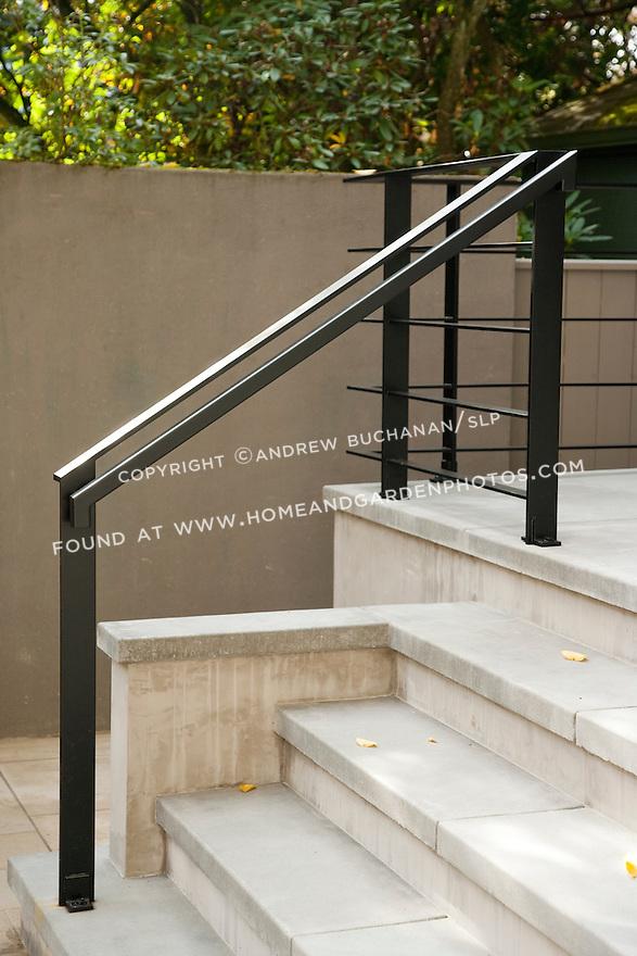 A sleek ,black metal railing contrasts the light grey stone steps.