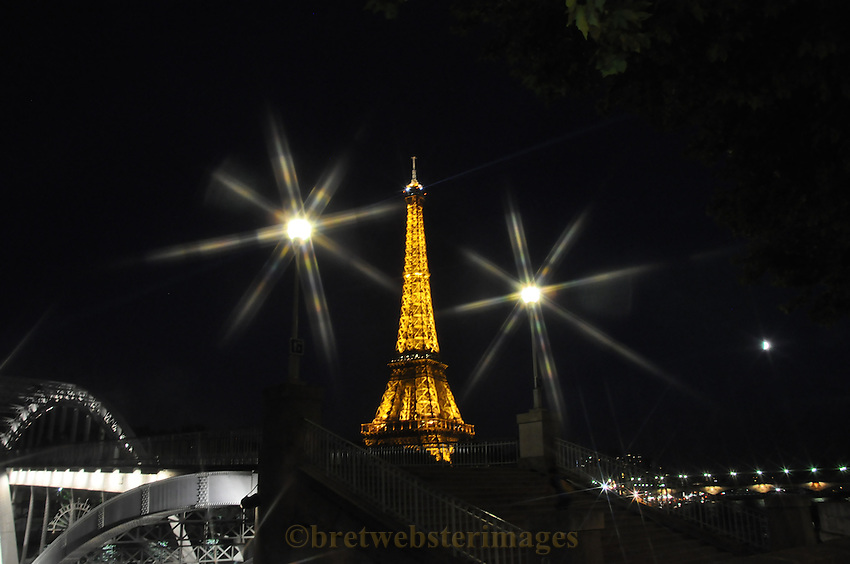 The Eiffel Tower at night in Paris, France framed by lights.
