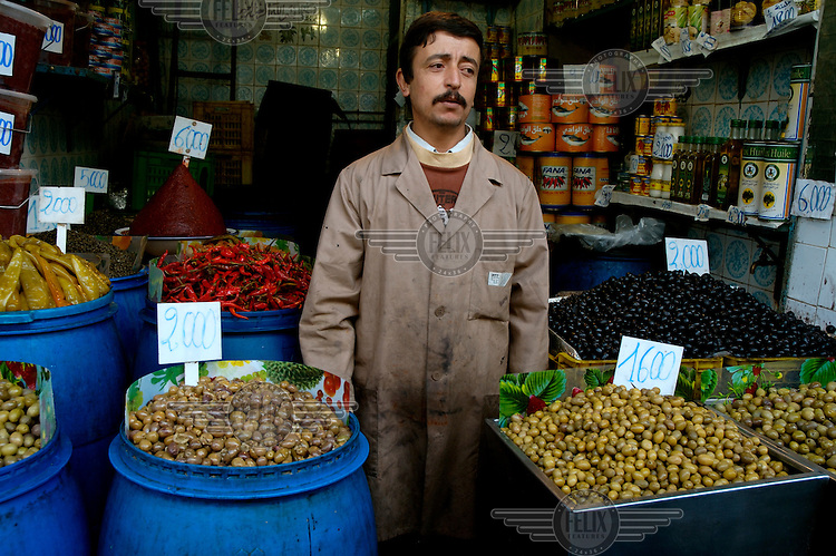 Man selling olives, peppers and chillies in his shop close to the Central Market.