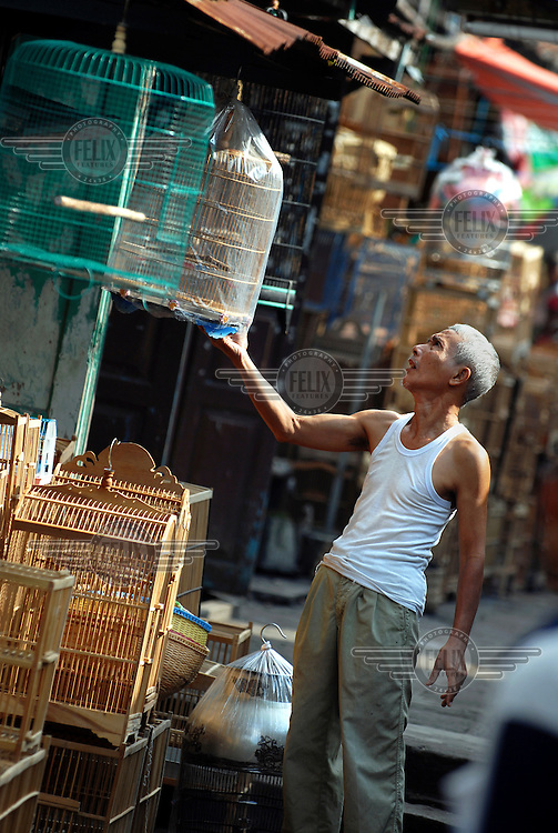 A man examines a caged bird for sale in the bird market.