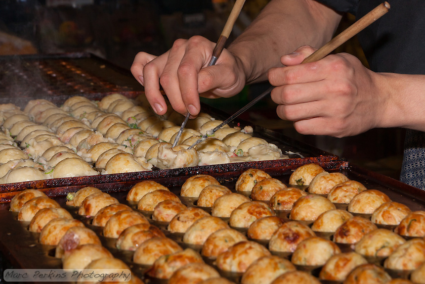 Chef Ryota Akai of Japan forms takoyaki during a demonstration of takoyaki cooking at Mitsuwa Market in Costa Mesa, California.  To form the takoyaki the batter is first cooked somewhat on the pans, and then the half-cooked batter is delicately (and quickly) rolled into a ball using chopsticks.  Compare all the images of this sequence to see the process; the last 7 of these frames were shot over only two seconds.