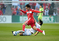 Vancouver midfielder Davide Chiumiento (20) takes down Chicago midfielder Gaston Puerari (18).  The Chicago Fire tied the Vancouver Whitecaps 0-0 at Toyota Park in Bridgeview, IL on May 7, 2011.
