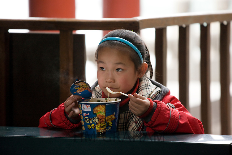 Young girl eating noodles at Summer Palace, Beijing. China has a one child family planning policy to limit population.