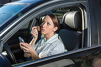 A business woman applies mascara make-up and text on her smart phone while driving a luxury car in Austin traffic.