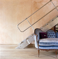 A French-style two-seater sofa upholstered in blue velvet is positioned infront of an industrial tubular steel staircase with open metal treads