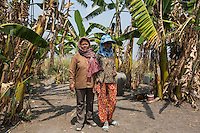 """Cambodia - Kampong Speu Province - Chheuon Khorn, 40, and her daughter Lak Chantrea, 15, from Trapang Khorn standing in the garden of their house. After their land was taken in 2010, the pair moved to Pis, in order to work as labourers inside the sugar plantation. """"The work is very hard and the pay is low. We work for ten hours a day and get 3,5 USD. It's like forced labour"""", complains Chheuon. In exchange for her two hectares of land, Chheuon got a piece of land of 40x50 metres for her house, plus a compensation of 125 USD. Her daughter Lak, who would like to become a teacher, works in the plantation as well."""