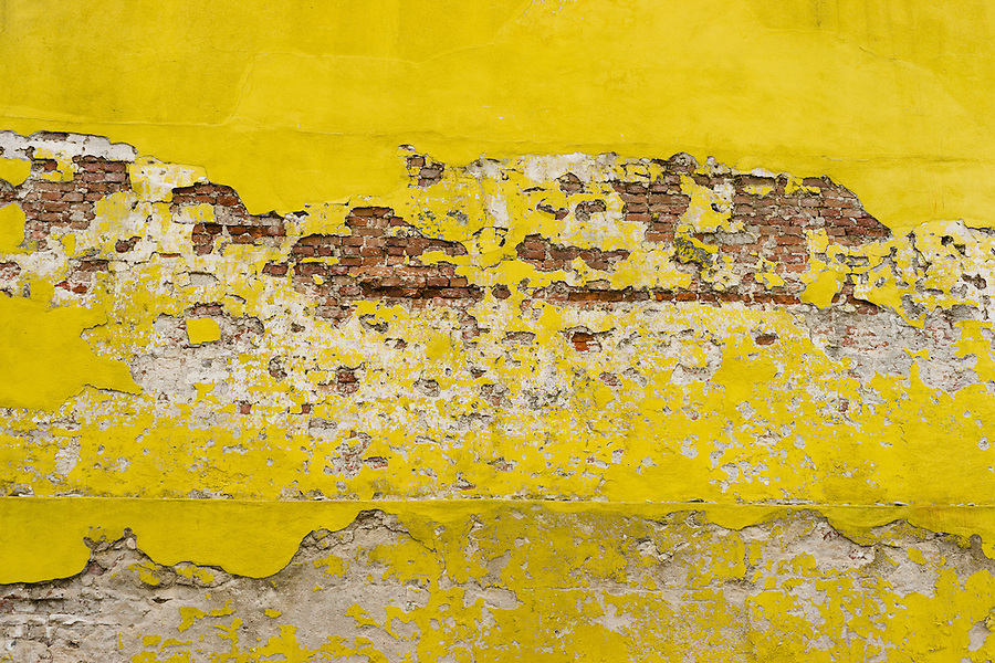 grungy old bricj wall with worn yellow plaster and paint