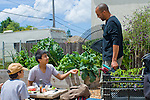 Berkeley CA Student at lunch, showing gardening teacher a vegetable that he grew