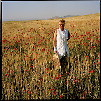 Liza Bruce stands in a field of wheat sprinkled with red poppies