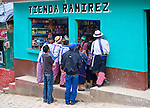 A group of local Guatemalans watch television through a tienda window on the street in Todos Santos Cuchumatan, Western Highlands, Guatemala