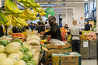 A worker stocks bananas and other fruit in the produce department in the new Whole Foods Market in Newark, NJ on opening day Wednesday, March 1, 2017. The store is the chain's 17th store to open in New Jersey. The 29,000 square foot store located in the redeveloped former Hahne & Co. department store building is seen as a harbinger of the revitalization of Newark which never fully recovered from the riots in the 1960's.  (© Richard B. Levine)