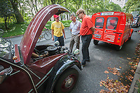Members of the Greater New York Citorën and Velosolex Touring Club inspect the engine of a 2CV Citroën automobile prior to their Bastille Day Rendez-Vous, seen on Riverside Drive in New York on Sunday, July 14, 2013. The parade of over a dozen Citroëns, including 2CV, DB series models, a truck and a traction avant started on Riverside Drive and traveled through the streets of Manhattan. The owners are dedicated to restoring and caring for their vehicles and share tips and information on repairing and restoring them. (© Richard B. Levine)