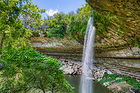 Another image of waterfall at Hamilton Pool located outside of Austin Texas. The is a natural pool created by an underground river that collasped and formed by erosion over  thousand of years.  The erosion created this cave with stalactite growing from the celling, a waterfall flowing over the limestone bolders along the waters edge with moss and the highlight the natural emerald green swimming hole.  The preserve includes about 232 acres of natural habitat and is home to the golden cheek warble.   This place draws a lot of people want to enjoy this place on a hot summer days but if you want to come be sure and call ahead and make reservation.  Over the years the place has been loved to death and you now need a reservation just to get in also it is also good to make sure it is open for swimming because it is a natural swimming hole no chemicals are added to the water so at times it get shut down due to high bateria counts.  This nature preserver is part  of the  Balcones Canyonlands Preserve and is a protected environment.