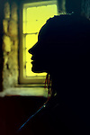 Female face in profile by window with yellow light