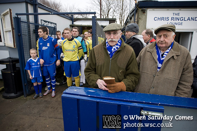 Glossop North End 0 Barnoldswick Town 1, 19/02/2011. Surrey Street, North West Counties League Premier Division. Two elderly Glossop North End supporters waiting for the teams to come out  before their club's game with Barnoldswick Town (in yellow) in the Vodkat North West Counties League premier division at the Surrey Street ground. The visitors won the match by one goal to nil watched by a crowd of 203 spectators. Glossop North End celebrated their 125th anniversary in 2011 and were once members of the Football League in England, spending one season in the top division in 1899-00. Photo by Colin McPherson.
