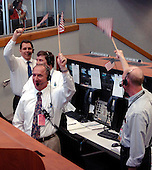 In Firing Room 4 of the Launch Control Center, employees wave American flags after the successful launch of Space Shuttle Discovery on mission STS-121.&nbsp; Liftoff was on-time at 2:38 p.m. EDT.&nbsp; During the 12-day mission, the STS-121 crew of seven will test new equipment and procedures to improve shuttle safety, as well as deliver supplies and make repairs to the International Space Station. Landing is scheduled for July 17 at Kennedy's Shuttle Landing Facility. Photo Credit: &quot;NASA/Bill Ingalls&quot;