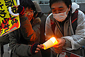 Tokyo, Japan - March 11: A man tried to give his fire to a woman's candle in front of the Diet Building at Chiyoda, Tokyo, Japan as a demonstration against nuclear power on March 11, 2012. More than 10,000 people held the candles and hands of next people to make a &quot;Human Chain.&quot; As this day was one year anniversary of Great East Japan Earthquake and Tsunami, there were many demonstrations held in the city.