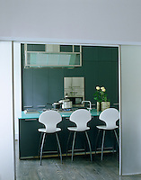 A glass encased extractor is suspended over the glass-topped kitchen island which houses the hob and sink and doubles as an informal dining area