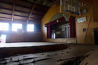 The collapsed floor of a school gym in an elementary school abandoned during the evacuation of Namie, Fukushima Prefecture, Japan, August 2, 2013. The town of Namie was evacuated following the nuclear accident of March 2011. Residents can only return for short periods to tend to their former homes and pick up belongings, and are not permitted to stay overnight.