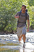 man hiking in a river