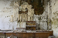 Concert hall with water damaged soviet relief sculpture and piano.<br />