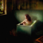 A young woman sitting alone in a small bath in a dark room