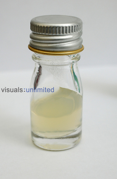 Small clear glass bottle containg a clear liquid. Royalty Free