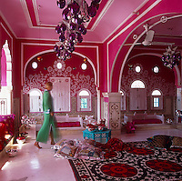 Liza Bruce strolls through the vibrant pink living room with its eclectic and colourful collection of objects and textiles