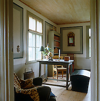 Simple antique furniture and bare floorboards create a pleasingly austere feel in the study of this country house