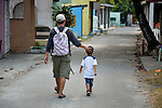 """A father walks his son through the Manila North Cemetery. Hundreds of poor families live here, dwelling in and between the tombs and mausoleums of the city's wealthy. They are often discriminated against, and many of their children don't go to school because they're too hungry to study and they're often called """"vampires"""" by their classmates. With support from United Methodist Women, KKFI provides classroom education and meals to kids from the cemetery at a nearby United Methodist Church."""