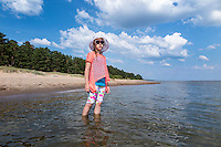 Young girl standing in water at Kauksi beach. Lake Peipsi in Estonia.