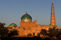 General view of Pahlavan Mahmud Mausoleum, 14th-16th century, Khiva, Uzbekistan, pictured at sunset on July 5, 2010. Visible are its blue tile-covered dome which commands Khiva's skyline and on the right the Islam Hodja minaret, 1910. Commissioned by the reforming Grand Visier, Islam Khodja, the minaret is 44.8 metres high, tapering towards the top, its ochre brick alternating with bands of decorative blue and white tiles. It is the final architectural achievement of the Khanates.