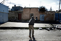 SYRIA - Al Qsair. A Syrian reporter as he is filming clashes between Free Syrian Army and Regime Army, in Al Qsair, on January 28,  2012. Al Qsair is a small town of 40000 inhabitants, located 25Km south-west of Homs. The town is besieged since the beginning of November and so far it counts 65 dead.In all Syria there are hundreds of non-professional reporters who without experience and without proper gear keep documenting, day after day, the crackdown of the regime. This series of pictures is dedicated to them... to this colleagues who among every kind of difficulties and risks let know to the word their stories and drama.  ALESSIO ROMENZI