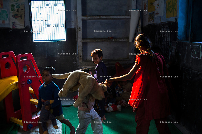 young children play with soft toys in the Guria Non-Formal Education center in the middle of the Shivdaspur red light district, Varanasi, Uttar Pradesh, India on 20 November 2013. Guria uses the soft toys as a form of therapy for the children of the women in prostitution and also use it as signals of the children's emotional wellbeing.