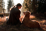 A woman and her dog (golden retriever) share a quite moment at sunset in Eldorado National Forest, California