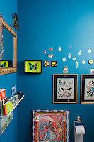 "On this wall painted a ""Biscay Bay"" blue is displayed a collection of framed butterflies"