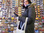 a persian woman looks at the camera as she passes in front of a rack of travel post cards.  taken at a souvenir shop while traveling in santa fe, new mexico.  horizontal composition.