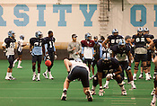 August 21, 2013. Chapel Hill, North Carolina.<br />  UNC Football Coach Larry Fedora leads his team in practice.<br />  Football practice at UNC was moved indoors due to inclement weather, just weeks before the start of the 2013-14 season.