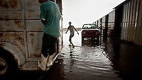 A young man walks through a flood caused by a heavy rainstorm at a local horse race track in Dodge City, Kansas.