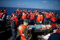 Sailors on board the USNS Comfort, a naval hospital ship, hold an abandon ship drill with a fake patient before their arrival to help survivors of the earthquake in Haiti on Tuesday, January 19, 2010 in the Caribbean Sea.
