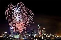 Fireworks explode over the Charlotte NC skyline as the city celebrated the July 4th holiday in 2013. Photographer has fireworks celebrations in Charlotte from multiple years. The collection of Charlotte NC fireworks photos show different perspectives and weather conditions.