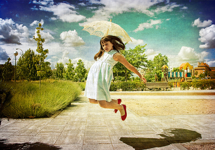 A young girl wearing a white summer dress with red shoes holding a sun shade jumping into the air