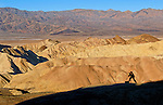 Photographer catching the perfect shot of sunrise at Zabriskie Point in Death Valley National Park in California.