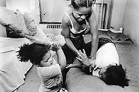 "USA. New York City. Spanish Harlem. Chichi (L), Lady and Bente (R), three sisters play together on a bed. Teddy bear. The Puerto Rican family lives below the poverty line and receives public assistance (AFDC, Home Relief, Supplemental Security Income and Medicaid). The family resides in units managed by the New York City Housing Authority (NYCHA) which provides housing for low income residents. NYCHA administers rental apartments in facilities, popularly known as ""projects"". Spanish Harlem, also known as El Barrio and East Harlem, is a low income neighborhood in Harlem area. Spanish Harlem is one of the largest predominantly Latino communities in New York City. 20.06.88 © 1988 Didier Ruef .."