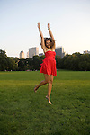 A young woman, wearing a red sundress,  jumps for joy in an urban park.