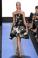 Kristy walks runway in a carbon black splatter print faille strapless hi-low cocktail dress, by Monique Lhuillier, from the Monique Lhuillier Spring 2012 collection fashion show, during Mercedes-Benz Fashion Week Spring 2012.
