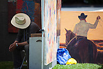 a vendor relaxes next to a painting featuring a cowboy at the 38th annual Los Altos Rotary's Fine Art in the Park show May 18.