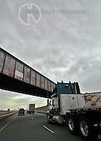 Americana Series: Road Trip<br /> <br /> Empty load passing  under the Santa Fe Railroad bridge.