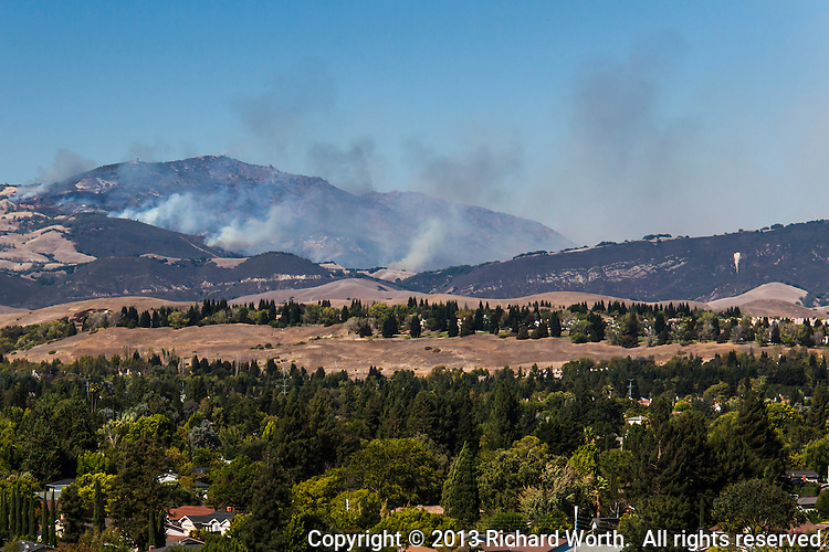 White smoke means  natural, untreated, wood and grass are burning.  Smoke rises from the Mount Diablo fire, viewed from a city street in San Ramon, CA, seven miles away at 3:30 PM local time, Monday, Sept. 9, 2013.
